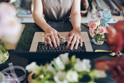 Close-up of unrecognizable female florist standing at desk and typing on laptop while working with online orders