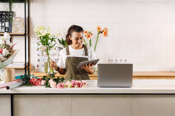 Florist using digital tablet in flower shop. Woman making a bouquet at the counter. stock photo