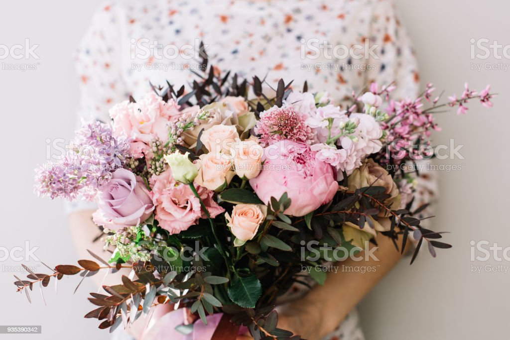 Florist woman holding a beautiful fresh blossoming flower bouquet of peony, roses, lilac, eustoma, mattiola in pink and lavender colors on the grey wall background стоковое фото