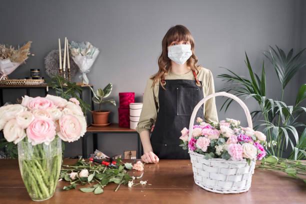 femme fleuriste dans un masque médical pour la protection contre le coronavirus. concept pandémique, travaillant pendant une épidémie. petit magasin de fleurs. livraison de fleurs. - fleuriste photos et images de collection