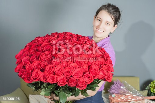 istock Florist woman prepares a big bouquet of red roses 512098126