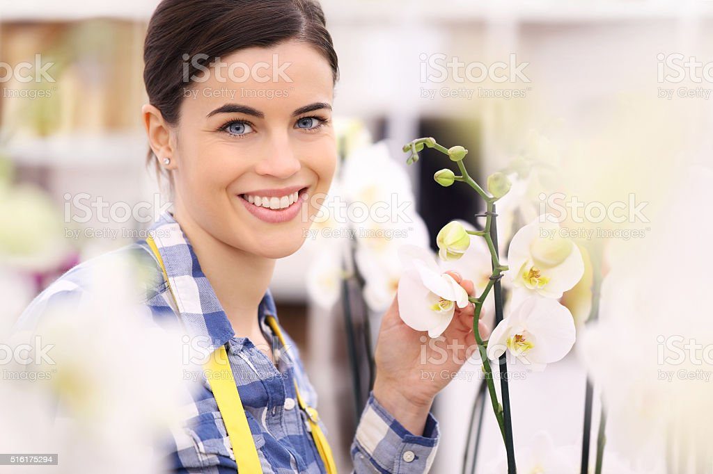 florist woman smiling with flowers orchids stock photo