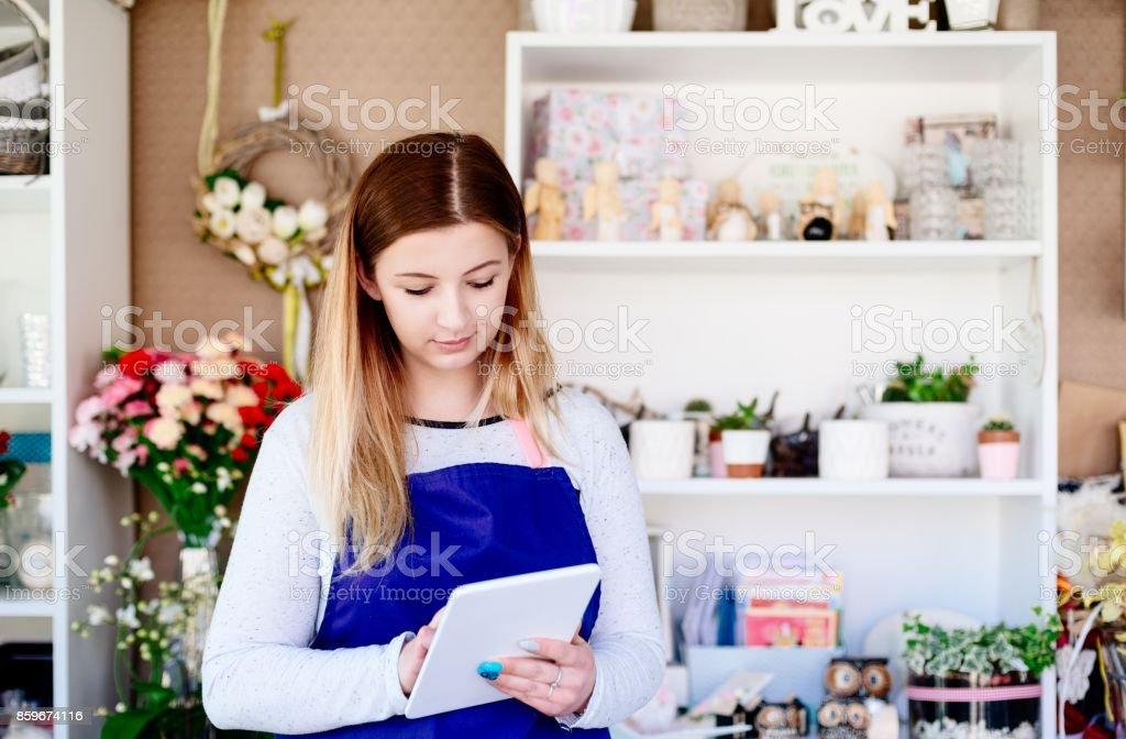 Florist woman taking order online by tablet. stock photo