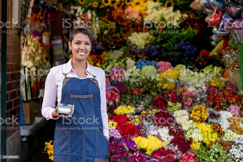 Happy female florist working at the flower shop and looking at the...