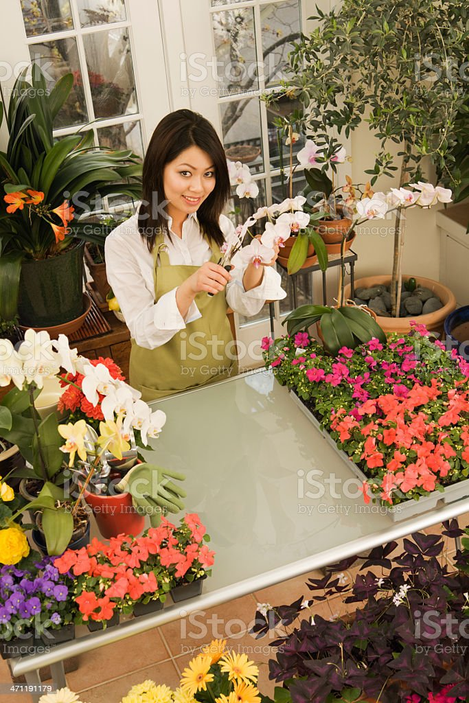 A small business owner of a retail flower shop. An Asian woman...