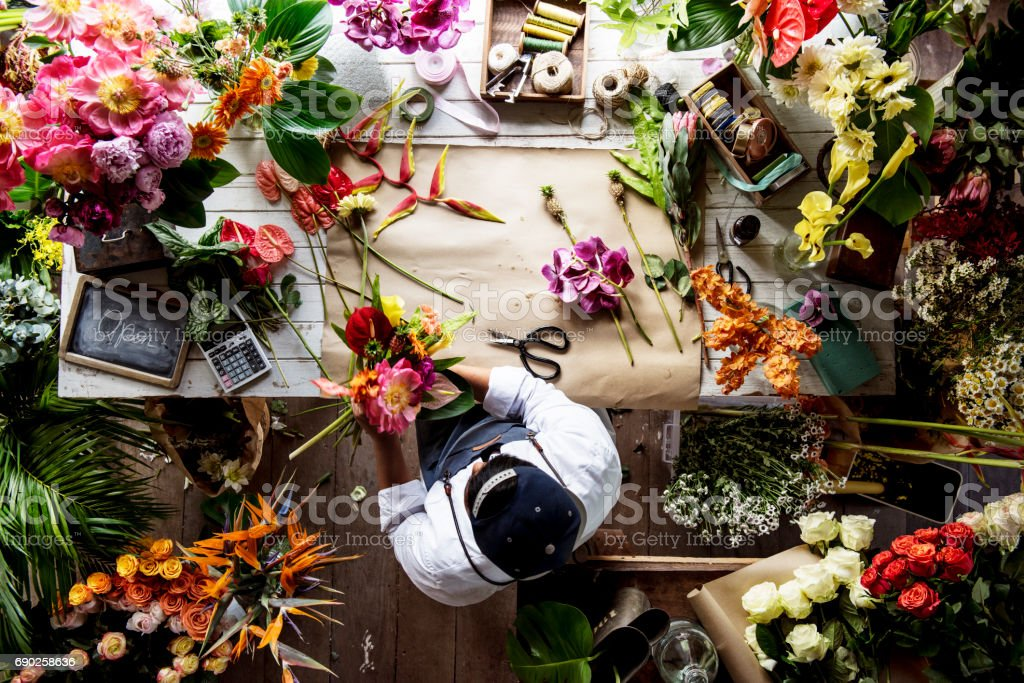 Florist working on flower arrangement among the flower stock photo