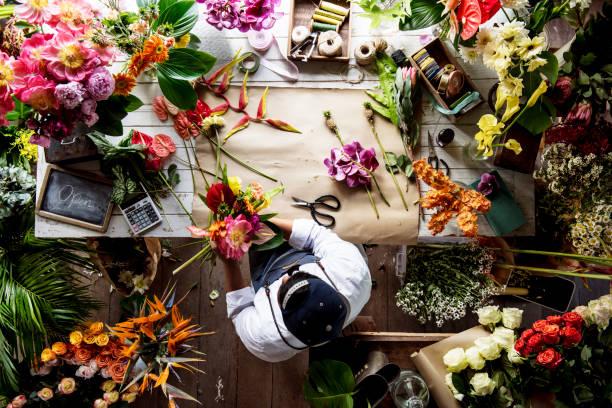 florist working on flower arrangement among the flower - fleuriste photos et images de collection
