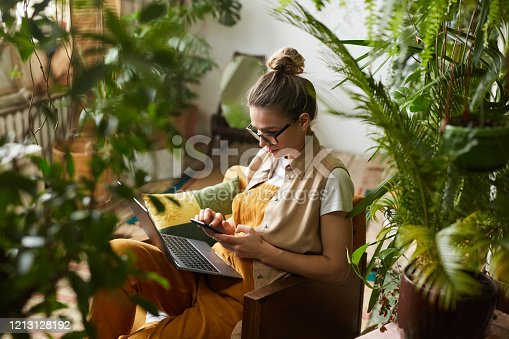 Young florist in eyeglasses sitting on armchair with laptop computer on her knees and using mobile phone in the room with plants
