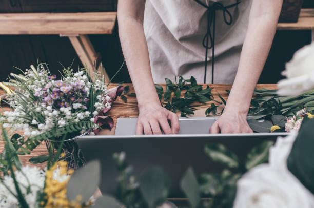 fleuriste de travail avec ordinateur portable - fleuriste photos et images de collection