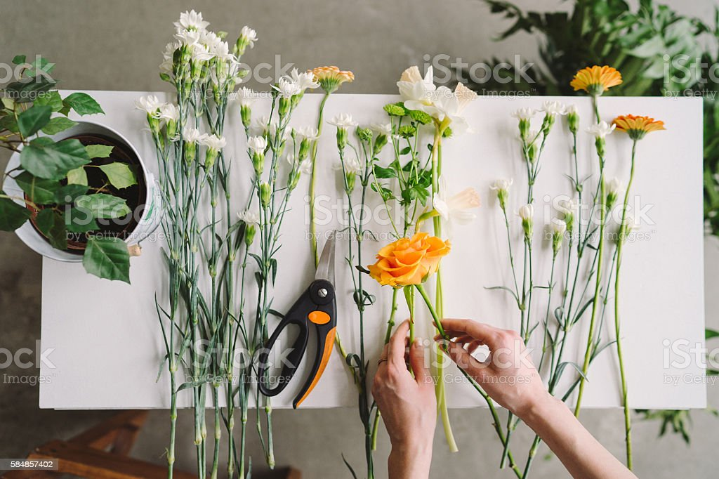 Florist workspace: caucasian woman making floral decorations stock photo