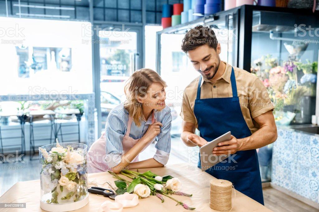 floristas con tableta digital en la tienda de la flor - foto de stock