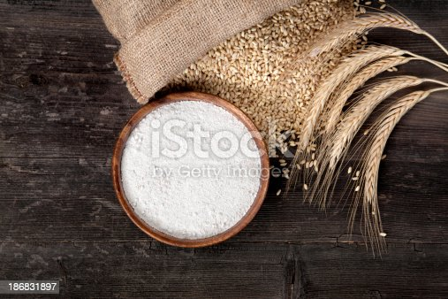 Flour and wheat grains with wheat ears on wooden background