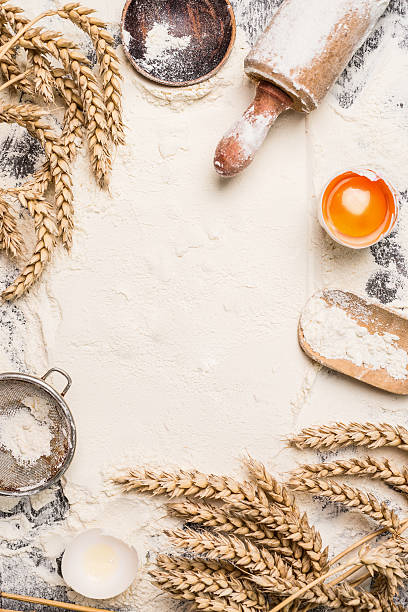 flour baking background with egg, rolling pin and wheat ear stock photo