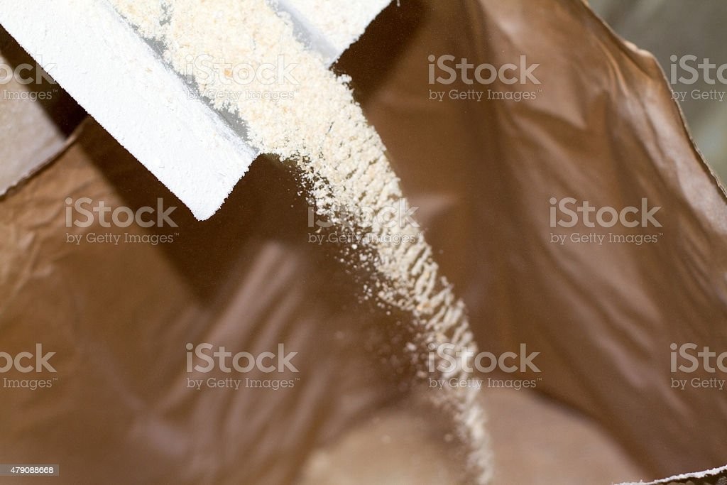 Flour Being Milled: Falling into Brown Paper Sack (Close-Up) stock photo