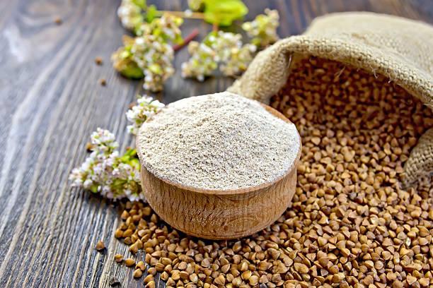 flour buckwheat in bowl with cereals and flower on board - boekweit stockfoto's en -beelden