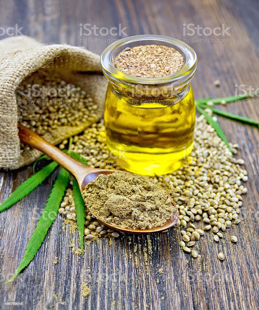 Flour hemp in spoon with oil and bag on board stock photo