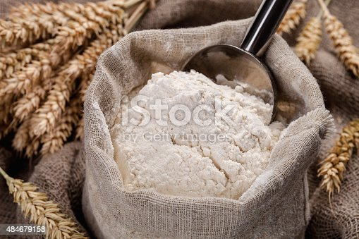 Flour in a bag on the table and spikelets.