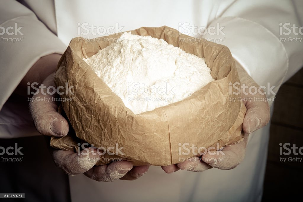 Flour in the womans hand. Selective focus. Toned stock photo
