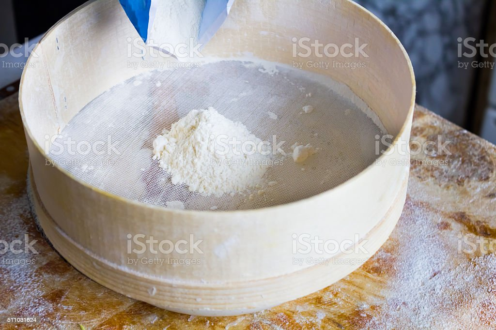 Flour is sifted through a wooden sieve stock photo