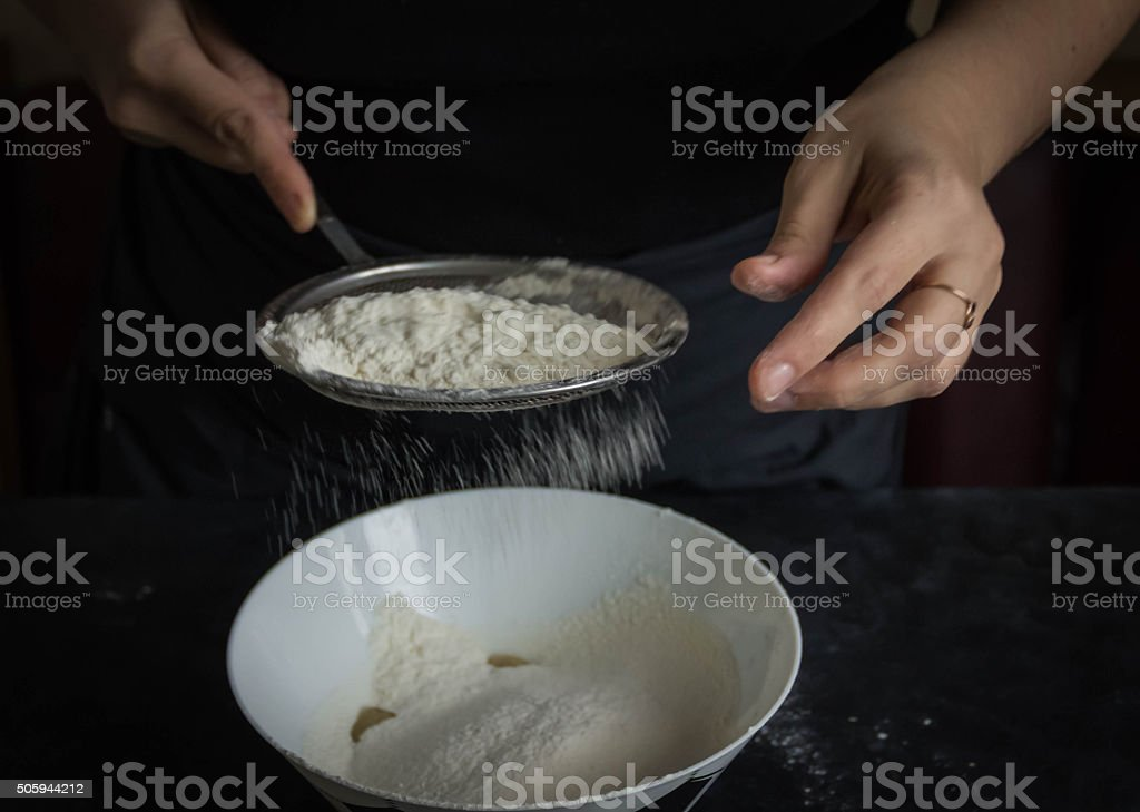 Flour sifting through a sieve for a baking hands stock photo