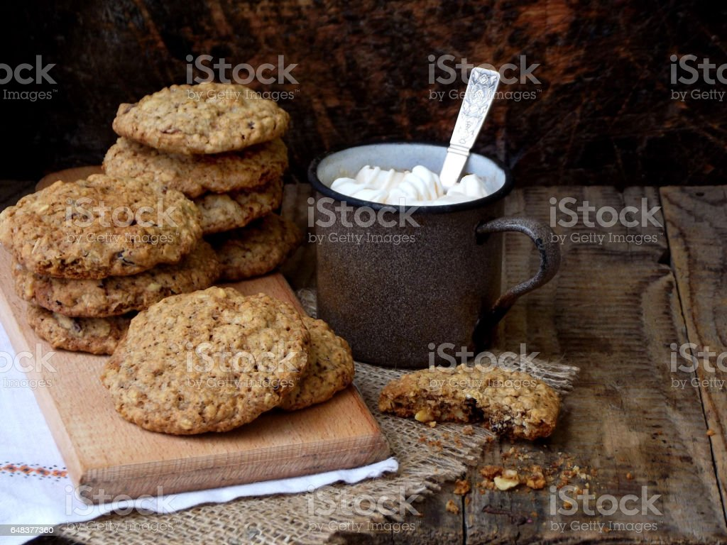 Flourless gluten free peanut butter, oatmeal, dried fruits cookies and cup of cocoa with marshmallows on wooden background. Horizontal. Copy space stock photo