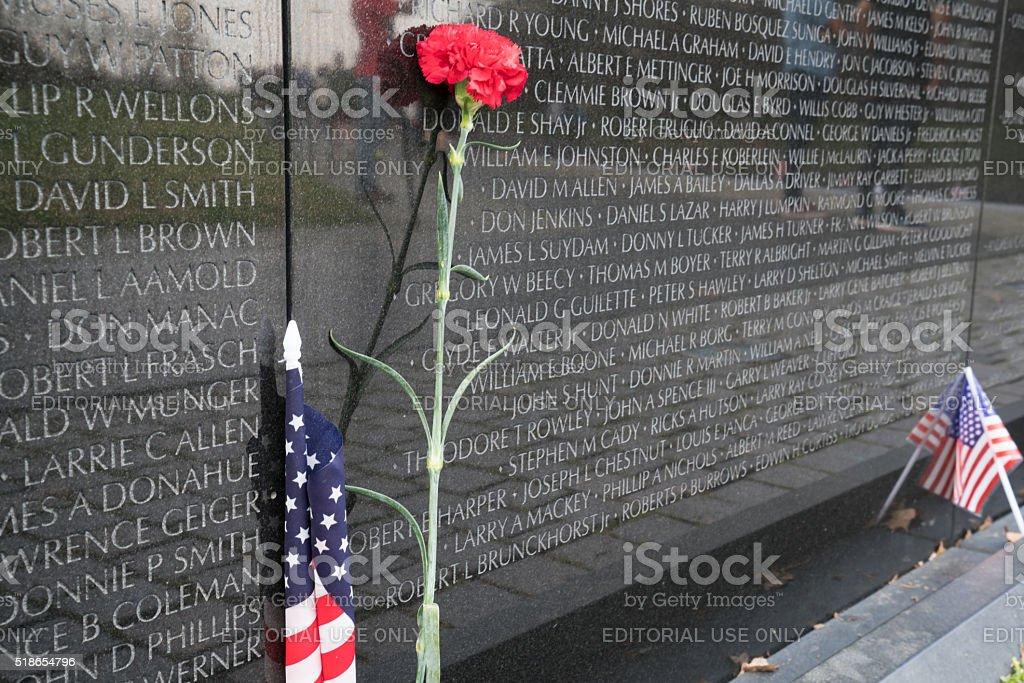 Flower and American Flag at Vietnam Veterans Memorial stock photo