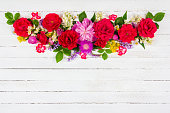 flower arrangement border of different field and garden flowers of roses, peonies and Jasmine on a white wooden background with a copy of the space, top view