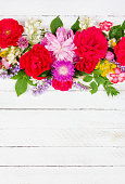 flower arrangement border of different wild and garden flowers of roses, peonies and jasmine on a white wooden background with copy space, top view