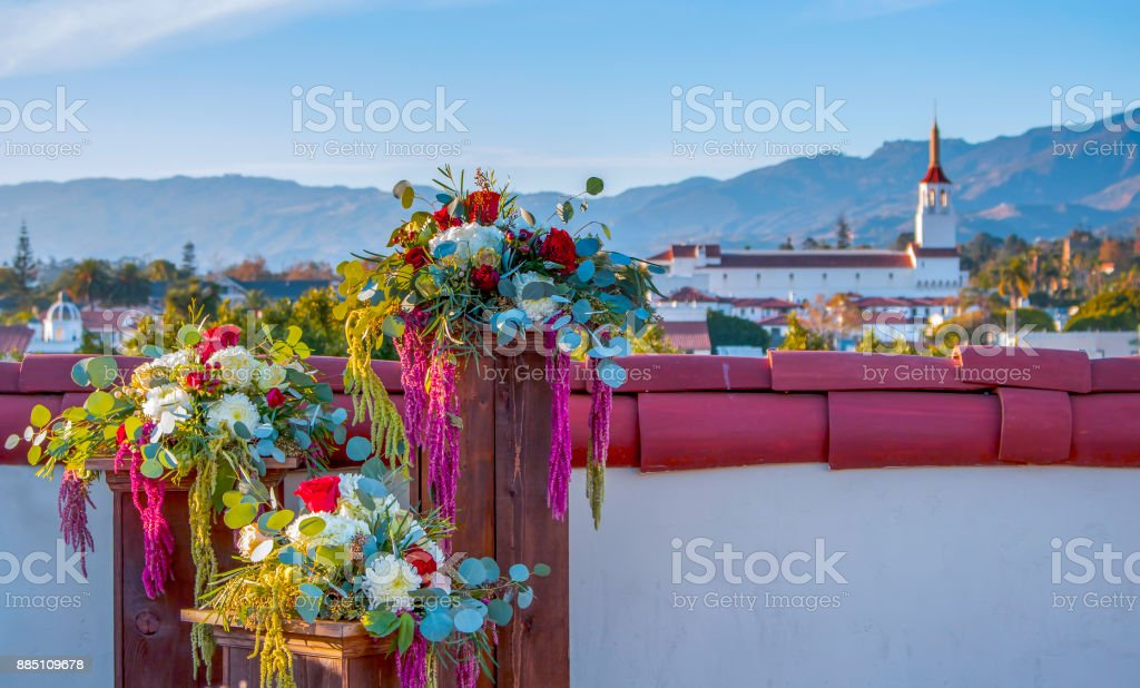 Flower Arrangements Sit on Rooftop in Santa Barbara California with Mountains and Buildings in Distance stock photo