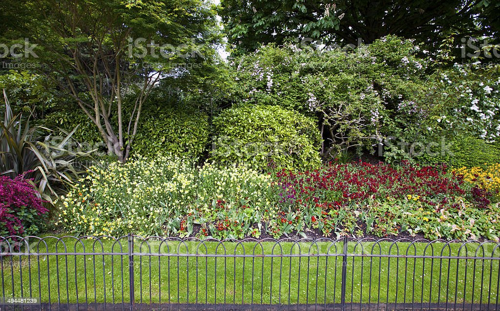 Flower bed and grass behind small fence royalty-free stock photo