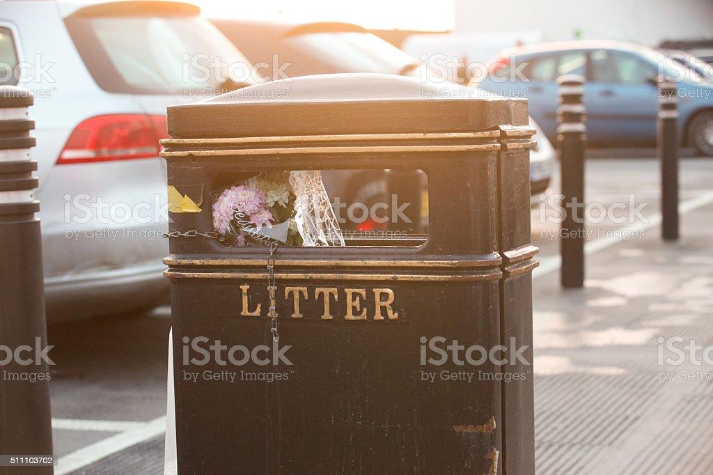 Flower bouquet dumped into a litter bin - rejected relationship? stock photo
