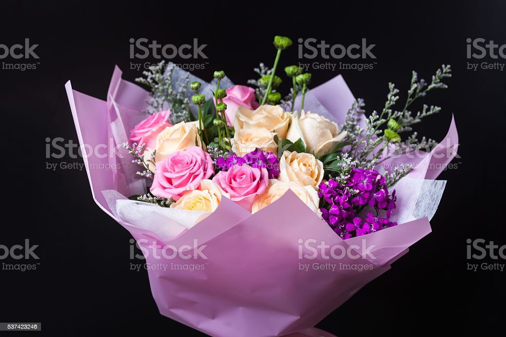 flower bouquet wrapped with paper standing on blackbround stock photo