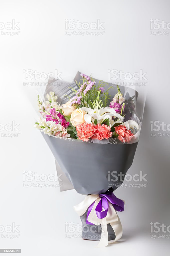 Flower bouquet wrapped with paper standing on white stock photo istock flower bouquet wrapped with paper standing on white royalty free stock photo mightylinksfo Gallery