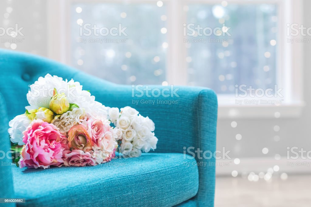 Flower bouquets in luxury home with turquoise chair stock photo