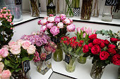 Flower bouquets in vases at store indoors. Colorful flowers