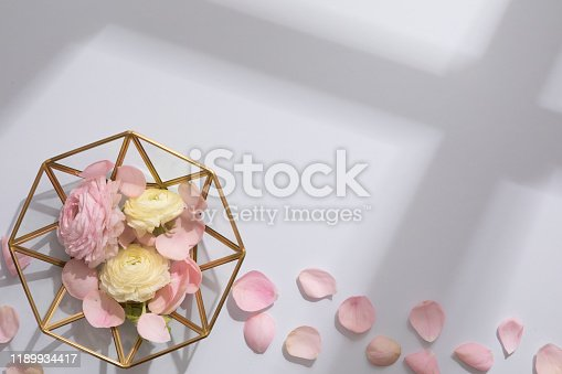 Flower composition on the pastel blue background. Overhead view with hard light and shadows