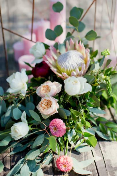 blume-komposition mit rosen und protea im bohème-stil - protea strauß stock-fotos und bilder