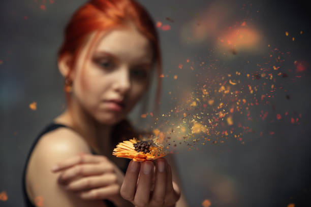 flower crumbling in the hands of a red-haired young girl - disintegrate stock pictures, royalty-free photos & images