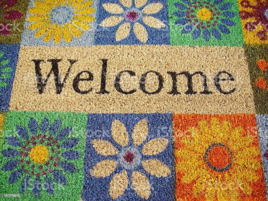 Flower decorated doormat with welcome sign stock photo