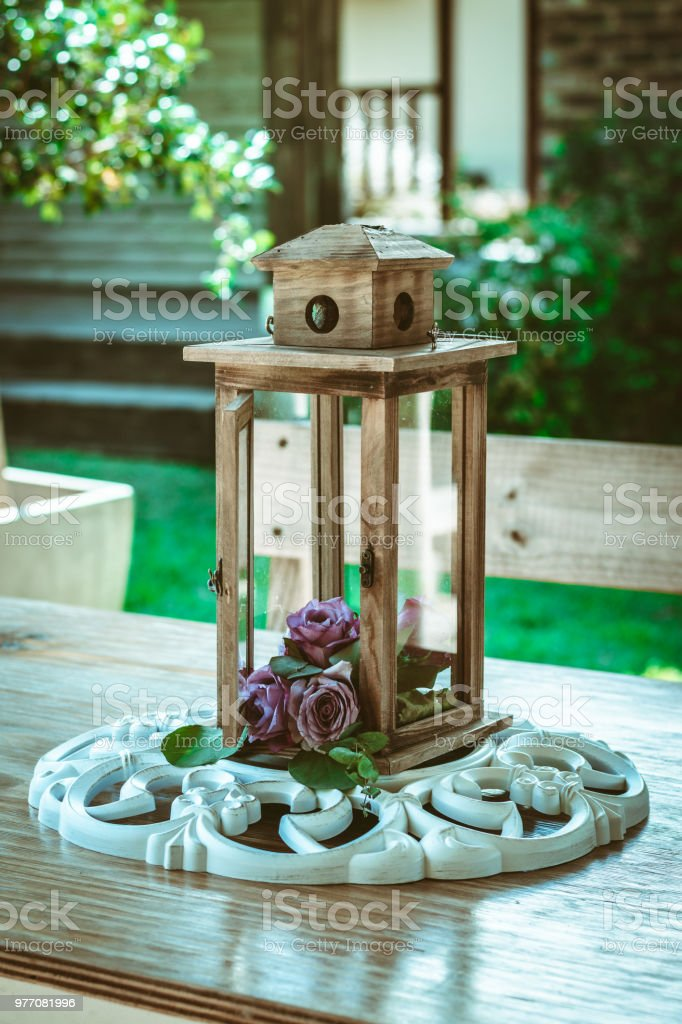 Flower Decorated Lantern Placed On A Wooden Table Outdoors Stock