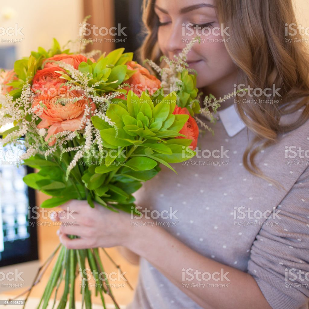 Flower delivery to the office. Young happy woman smelling flowers royalty-free stock photo