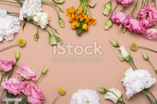 Flower flat lay for decorative design on beige background. Minimal romantic hipster concept, mockup background.