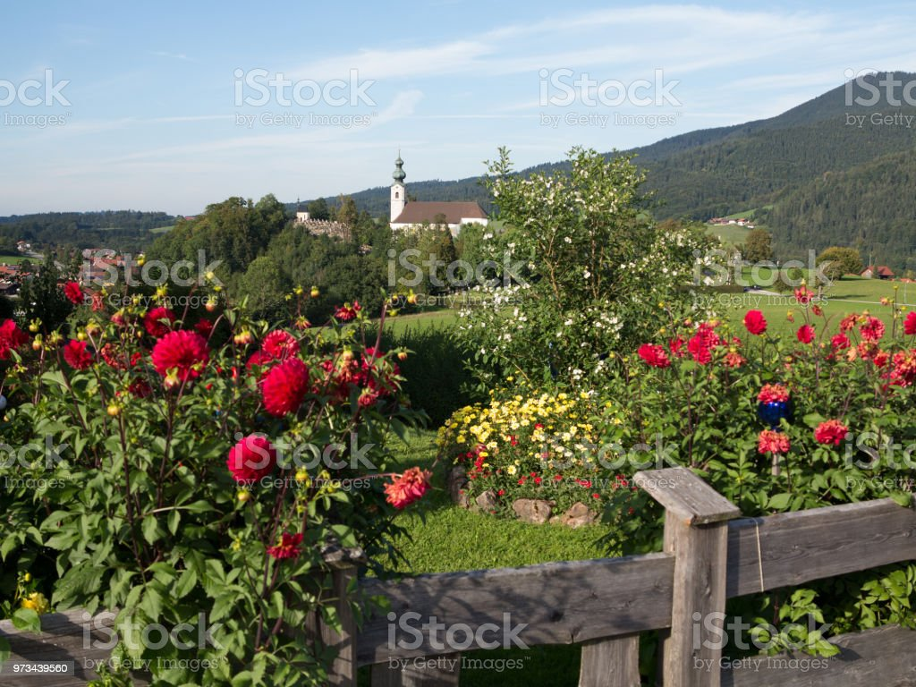 Flower garden in front of a Bavarian landscape with a church stock photo