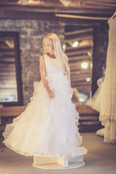 flower girl dreams of being bride at bridal shop - katiedobies stock pictures, royalty-free photos & images