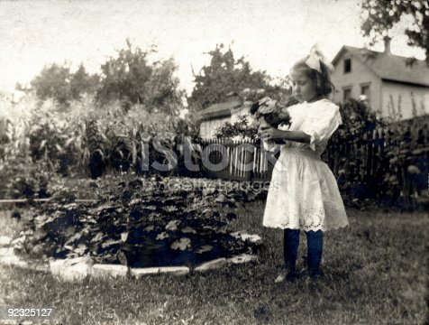 Vintage photo of a young girl with a bunch of flowers in her hands.