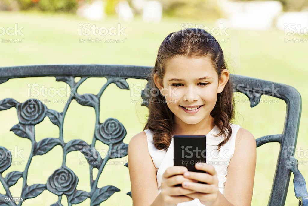 Flower Girl Using Mobile Phone While Sitting On Bench royalty-free stock photo