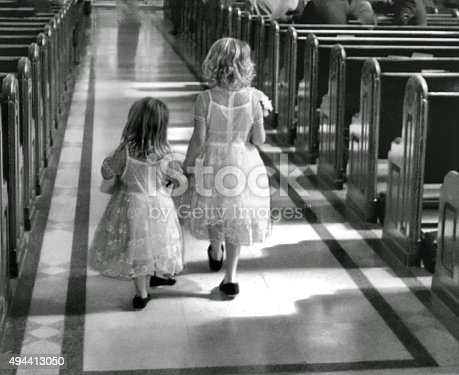 Two little gitls walk down the aisle in a wedding procession