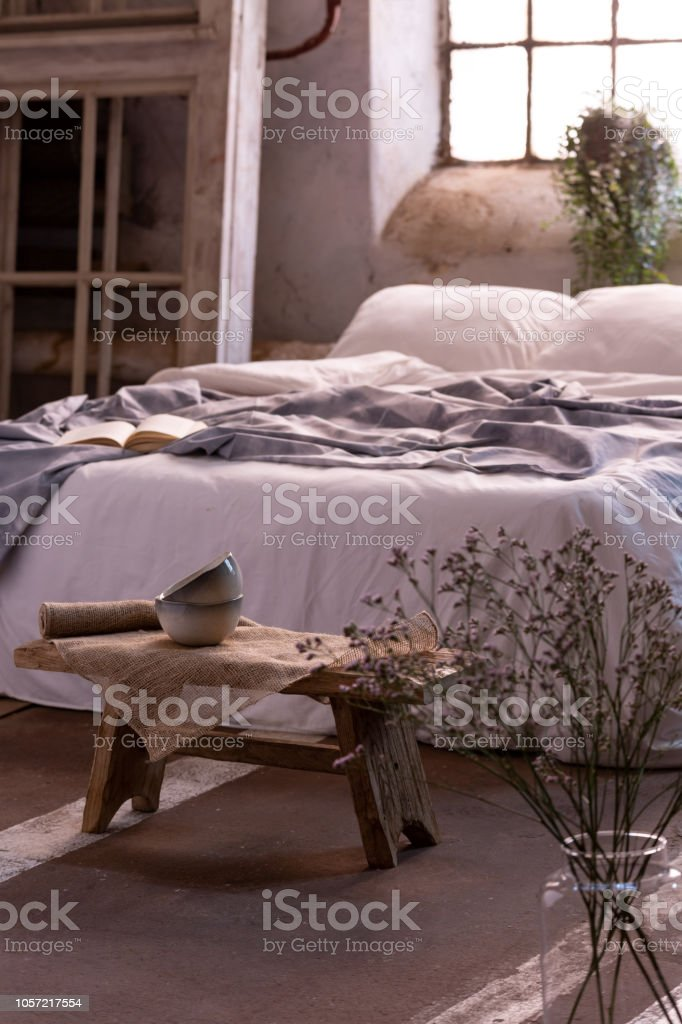 Flower In A Vase And Small Table In Front Of A Bed In A Bedroom