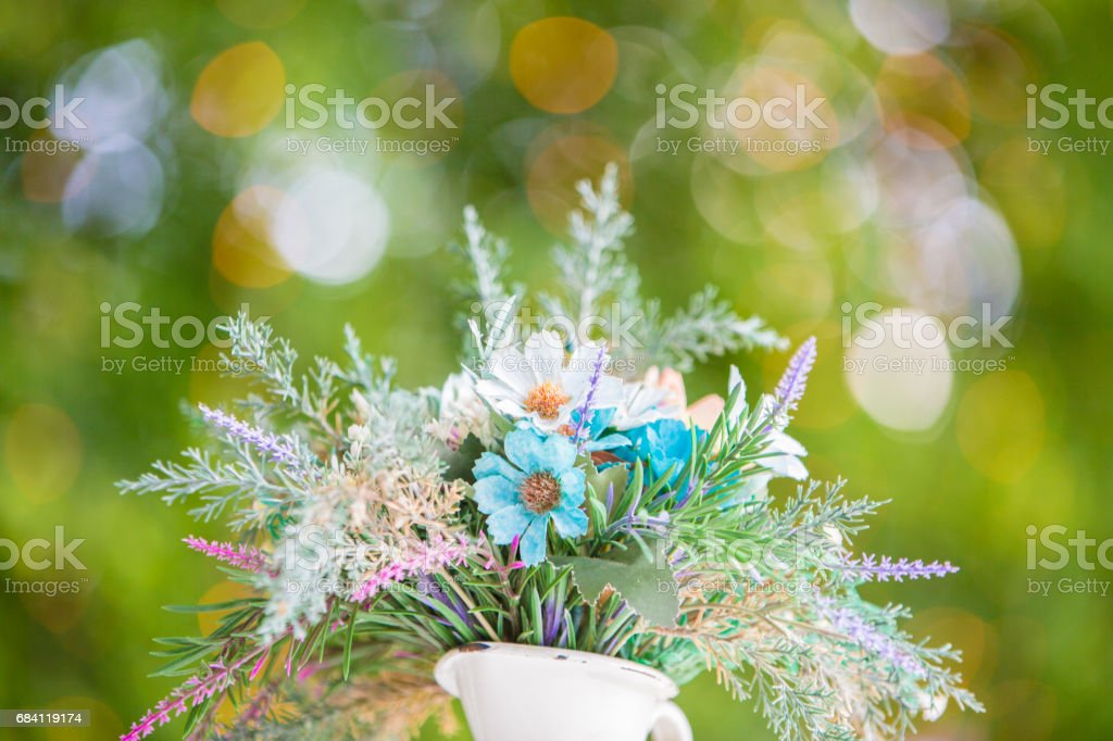Flower in vase on white table with orange color lighting bokeh on green background foto stock royalty-free