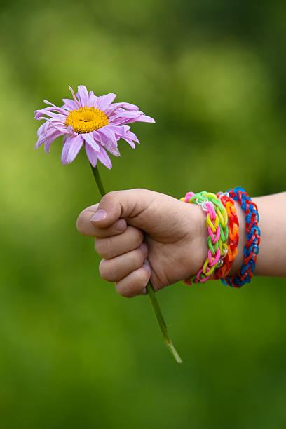 junges mädchen mit blumen in der hand mit gummiband armbänder - armband i gummi stock-fotos und bilder
